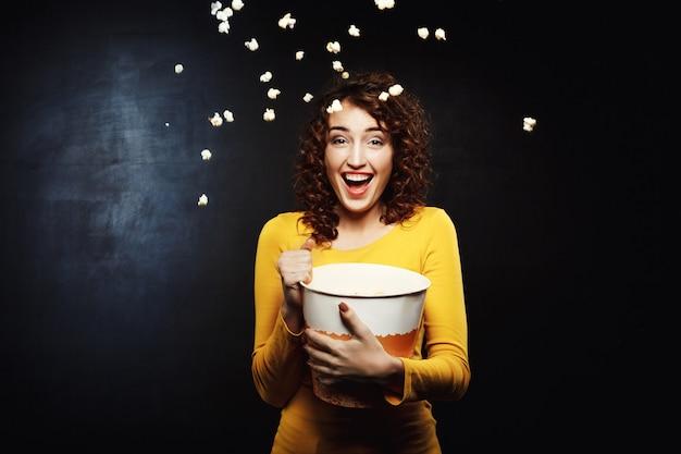 Lachende vrouw die popcorn overgeven in de lucht