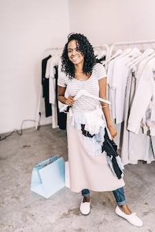 Lachende vrouw die trendy rok in winkel probeert