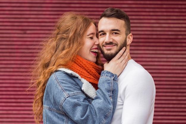Lachende vrouw die vriend vooraanzicht omhelst