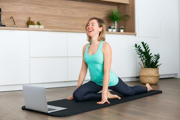 Lachende vrouw die zich uitstrekt voor de laptop terwijl thuis yoga online