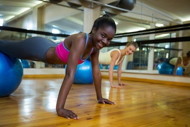 Lachende vrouw doet pilates-oefeningen op fitness bal met coach in fitness-studio
