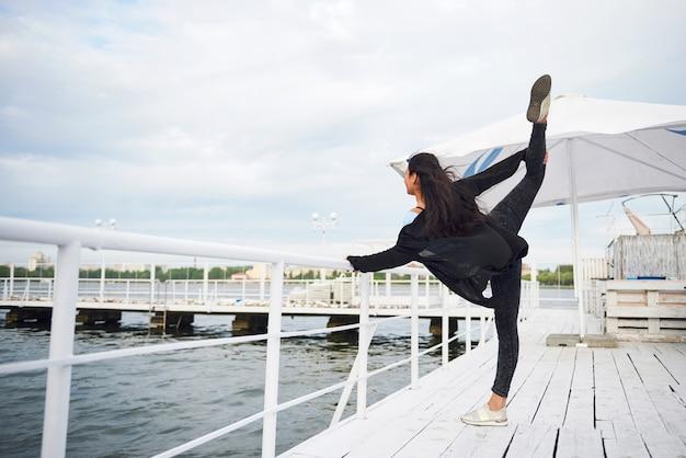 Lachende vrouw doet yoga oefening buiten op het strand pier.