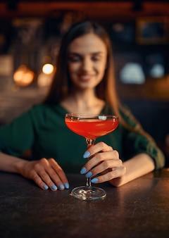 Lachende vrouw drinkt cocktail aan de balie in de bar. een vrouwelijke persoon in de kroeg, menselijke emoties, vrijetijdsactiviteiten, nachtleven