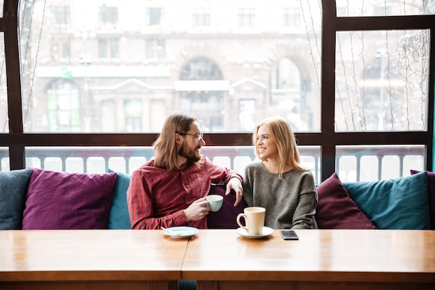 Lachende vrouw en bebaarde man vrienden zitten in café