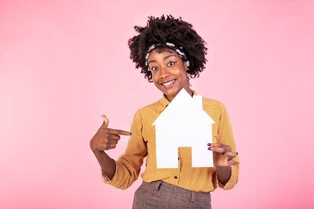 Lachende vrouw huis kopen, papier huis in handen houden en glimlachen, schulden betalen, staande witte achtergrond gelukkig