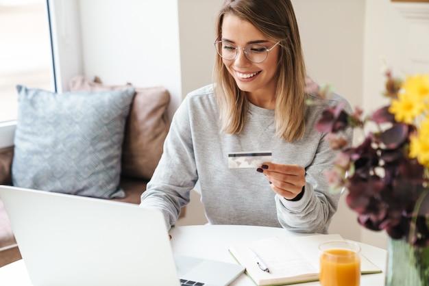 Lachende vrouw in bril met laptop terwijl ze een creditcard in de woonkamer vasthoudt