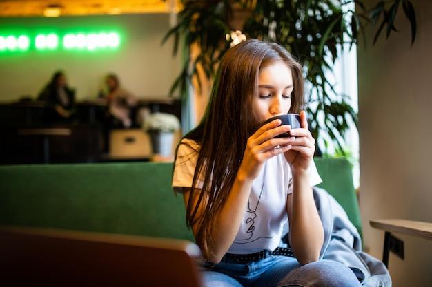 Lachende vrouw in een goed humeur met een kopje koffie zitten in café.