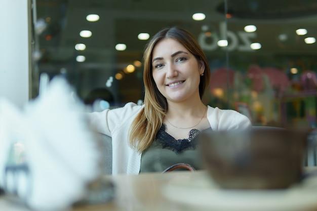 Lachende vrouw in een goed humeur met kopje koffie zitten in café.