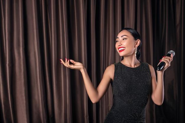 Lachende vrouw in een mooie jurk met een microfoon in haar hand