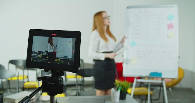 Lachende vrouw in gesprek met studenten via videoconferentie op tablet pc.