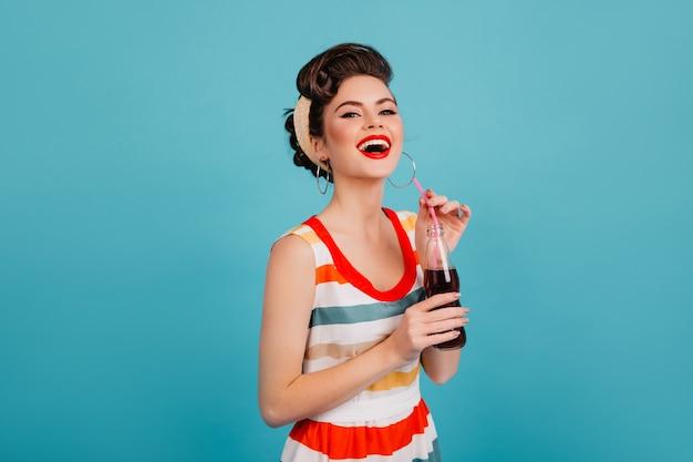 Lachende vrouw in gestreepte jurk frisdrank drinken. studio shot van gelukkig pinup meisje met drank geïsoleerd op blauwe achtergrond.