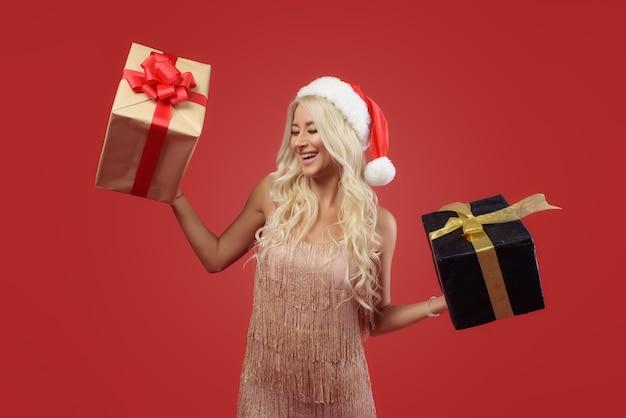 Lachende vrouw in gouden jurk en kerstmuts met stapel geschenkdozen geïsoleerd op de rode muur