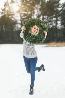 Lachende vrouw in grijze trui en spijkerbroek, poseren met de versierde krans van een nieuwjaar
