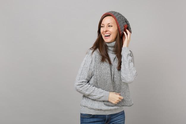 Lachende vrouw in grijze trui, muts sjaal opzij kijken, hand op het hoofd geïsoleerd op een grijze achtergrond. gezonde mode-levensstijl, oprechte emoties van mensen, concept van het koude seizoen. bespotten kopie ruimte.
