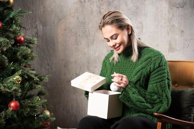Lachende vrouw in groene trui zitten en poseren met een geschenkdoos