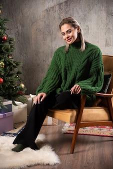 Lachende vrouw in groene warme trui zittend op de stoel en poseren