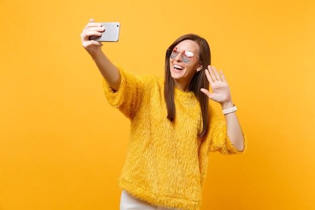Lachende vrouw in hart bril doen selfie schot op mobiele telefoon maken video-oproep zwaaiende hand voor groet geïsoleerd op felgele achtergrond. mensen oprechte emoties, levensstijl. ruimte kopiëren.