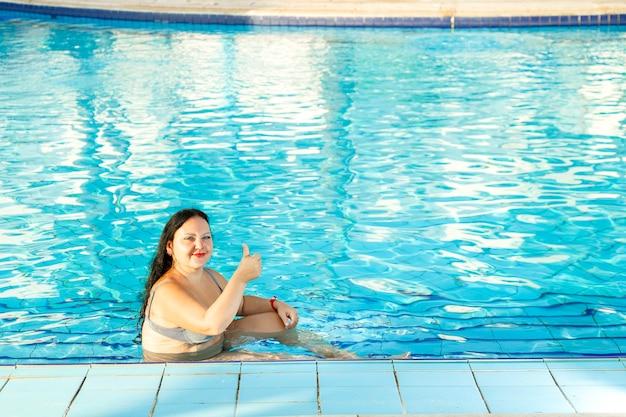 Lachende vrouw in het zwembad toont klasse. horizontale foto