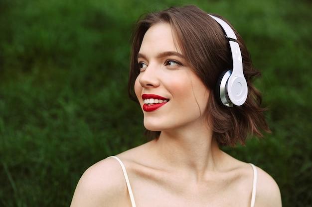 Lachende vrouw in jurk en koptelefoon luisteren muziek terwijl wegkijken en zitten in park