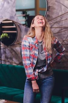 Lachende vrouw in marine shirt met krullend haar over witte muur. een brede glimlach en rode lippen.