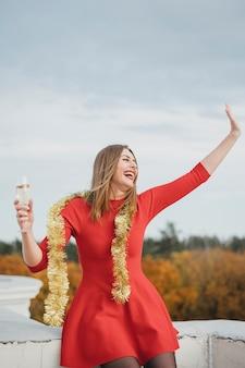 Lachende vrouw in rode jurk plezier op het dak