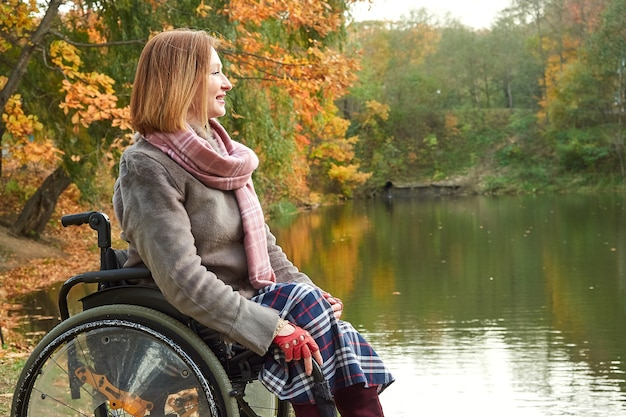 Lachende vrouw in rolstoel genieten van prachtig uitzicht op het meer in het park op herfstdag