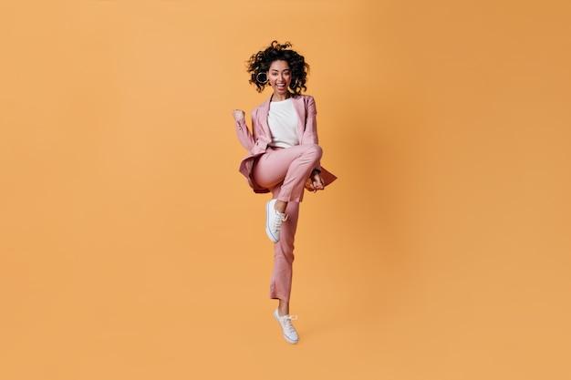 Lachende vrouw in roze pak met ja gebaar