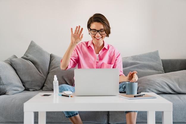 Lachende vrouw in roze shirt ontspannen zittend op de bank thuis aan tafel online werken op laptop vanuit huis