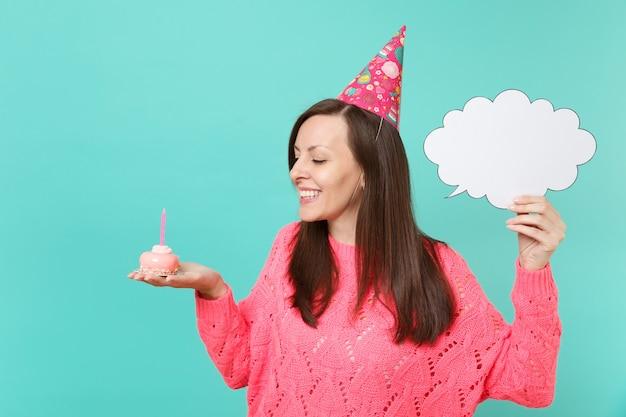 Lachende vrouw in verjaardagshoed op zoek op taart met kaars, houd lege lege say cloud, tekstballon voor promotionele inhoud geïsoleerd op blauwe achtergrond. mensen levensstijl concept. bespotten kopie ruimte.
