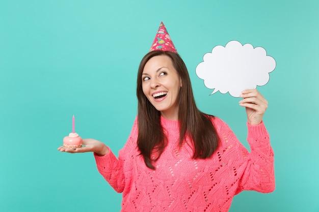 Lachende vrouw in verjaardagshoed opzoeken hold cake met kaars, lege blanco say cloud, tekstballon voor promotionele inhoud geïsoleerd op blauwe achtergrond. mensen levensstijl concept. bespotten kopie ruimte.