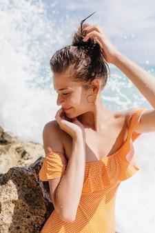 Lachende vrouw in vintage gele badmode poseren op het strand. buiten schot van kaukasisch meisje haar donkere haren aan te raken terwijl ze plezier hebben in de buurt van zee.