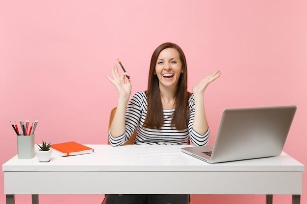 Lachende vrouw in vrijetijdskleding met potlood spreidende handen zitten, werken aan een wit bureau met een moderne pc-laptop