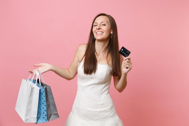 Lachende vrouw in witte jurk met creditcard en veelkleurige pakketten met aankopen na het winkelen