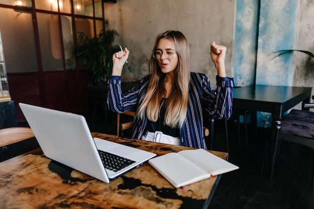 Lachende vrouw in zonnebril die met computer werkt. binnen schot van aantrekkelijk meisje in gestreepte jas met behulp van laptop.