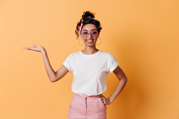 Lachende vrouw in zonnebril gebaren op gele muur