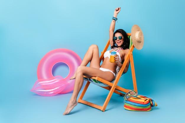 Lachende vrouw in zonnebril zittend op een ligstoel met hand omhoog