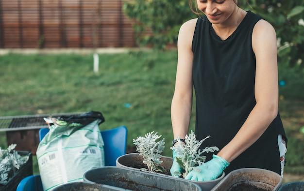 Lachende vrouw in zwart t-shirt voelt zich goed tijdens het planten van bloemen in pot thuis buiten