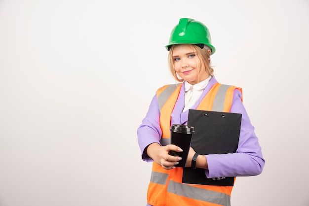 Lachende vrouw industrieel ingenieur in uniform met klembord en zwarte kop op wit.