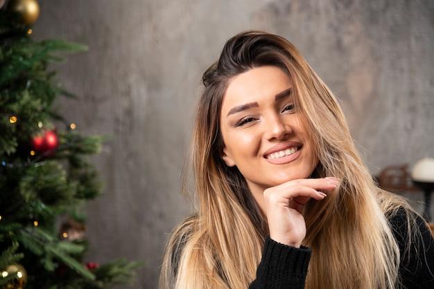 Lachende vrouw kijken naar de camera in gezellige kerst interieur. hoge kwaliteit foto