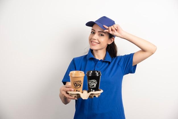 Lachende vrouw koerier met twee kopjes koffie.