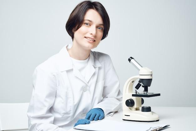 Lachende vrouw laboratoriumassistent microscoop onderzoek microbiologie wetenschap