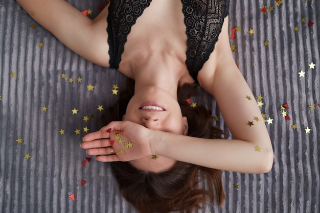 Lachende vrouw liggend op grijs zacht versierd met gouden confetti sterren.