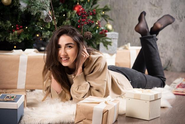 Lachende vrouw liggend op pluizig tapijt met kerstcadeautjes.