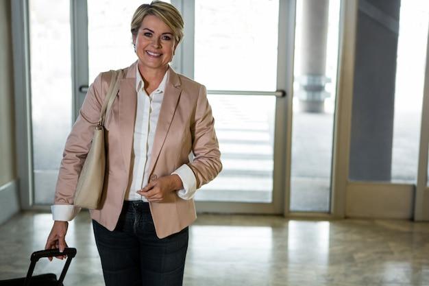 Lachende vrouw lopen met trolley tas in luchthaventerminal