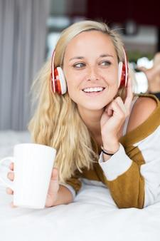Lachende vrouw luisteren muziek en thee drinken