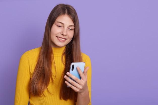 Lachende vrouw maakt gebruik van een mobiele telefoon, kijkt naar het apparaat met een charmante glimlach, draagt casual kleding.