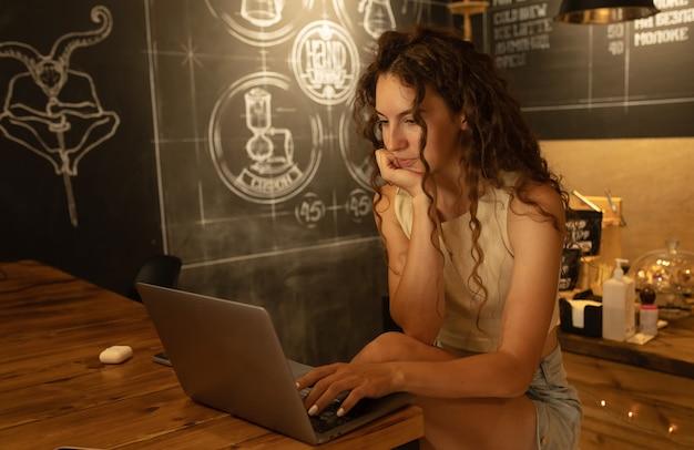 Lachende vrouw maakt gebruik van laptopcomputer, zit bij coffeeshop met kopje cappuccino en dessert