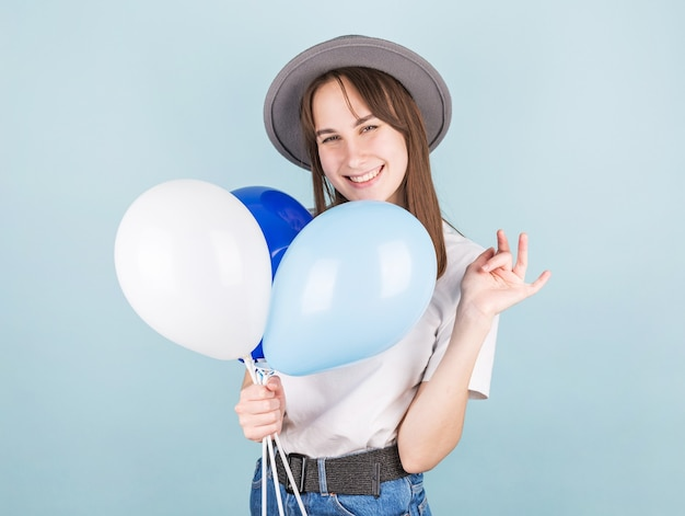 Lachende vrouw met ballon en camera kijken op blauwe achtergrond.