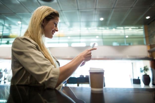Lachende vrouw met behulp van mobiele telefoon in wachtruimte