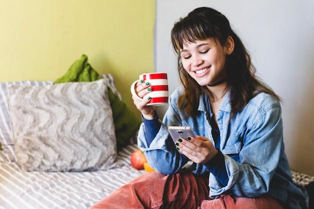 Lachende vrouw met behulp van telefoon op bed